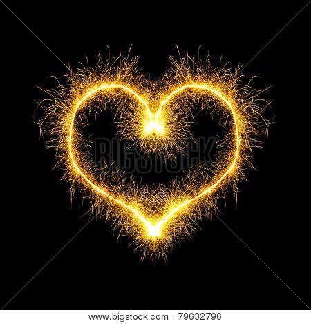 Sparking heart over black background