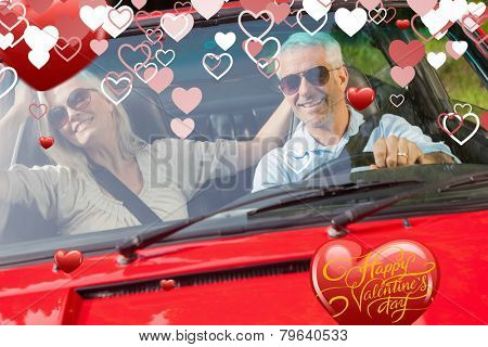 Happy mature couple in red cabriolet against happy valentines day