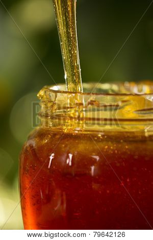 Close-up Shot Of Flowing Honey Over Yellow Background