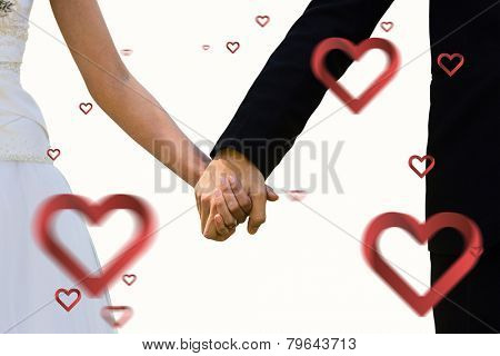 Mid section of newlywed couple holding hands in park against hearts
