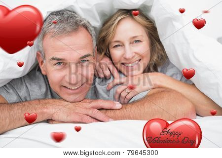 Loving couple under the duvet against heart hot air balloon