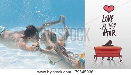 Cute couple kissing underwater in the swimming pool against love is in the air
