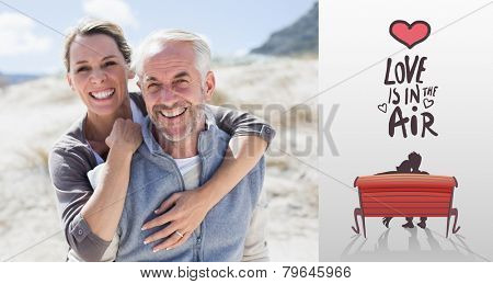Happy hugging couple on the beach looking at camera against love is in the air