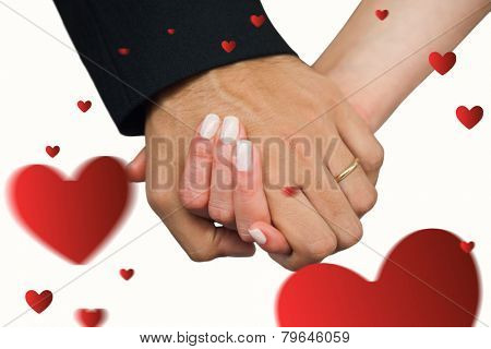 Newlyweds holding hands close up against hearts