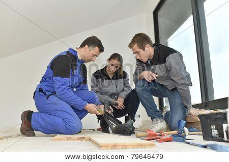 Carpenter with trainees installing wooden floor