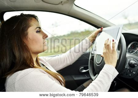 Woman driving and looking at roadmap on digital tablet