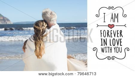 Couple wrapped up in blanket on the beach looking out to sea against valentines message