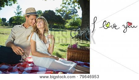 Cute couple drinking white wine on a picnic smiling at each other against i love you