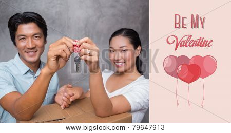 Happy couple holding house key and leaning on moving box against cute valentines message
