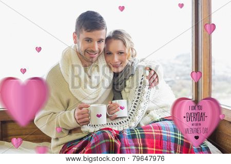 Loving couple in winter wear with cups against window against i love you everyday
