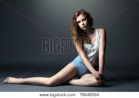 Skinny young model posing in studio, on gray