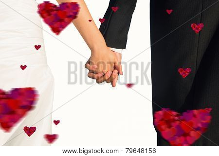 Close up of cute young newlyweds holding their hands against hearts
