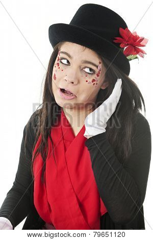 An attractive teen in red and black with a goofy expression as she straightens her hair under her top hat.  On a white background.