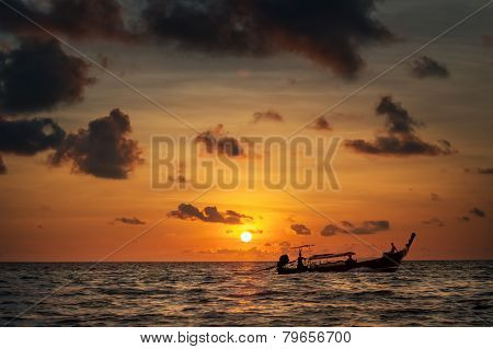 sunset with colorful sky and boat on the sea