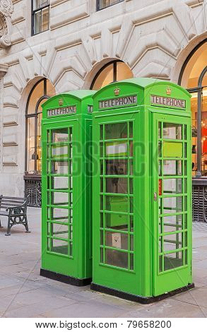 Green phone boxes in London city.