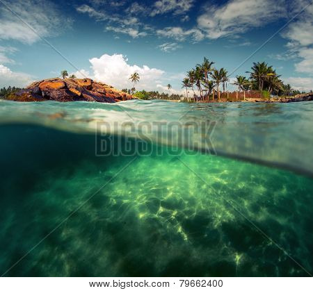 Split shot of the sandy bottom with rocks on the coast of Indian Ocean. Sri Lanka