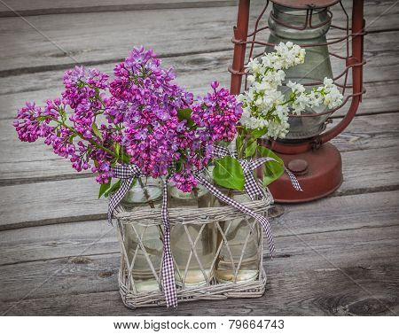 A Bouquet Of Lilacs And Old Kerosene Lamp