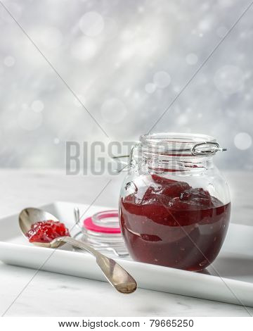 Cranberry sauce in glass jar on a white tray with spoon