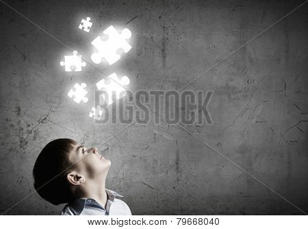 Young boy of school age looking at puzzle elements