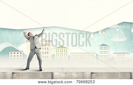 Young businessman wearing crown and carrying white blank banner. Place for text