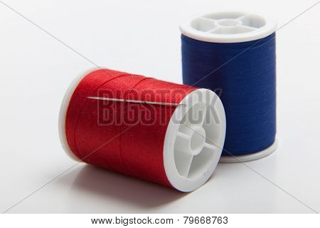 Spools of red and blue sewing thread with a sewing needle