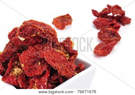 a pile of sun-dried tomatoes in a bowl on a white background