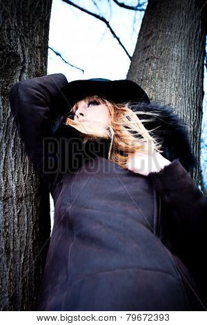 blonde woman in leather coat with fur and hat stand by tree, cold winter day