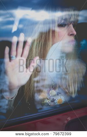 young woman portrait in the car behind the window, hand on glass looking away