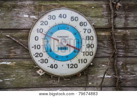 Vintage Thermometer showing 8 degrees fahrenheit on side of barn.