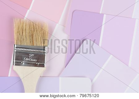 High angle closeup shot of a paint brush laying on a color paint chip samples. Horizontal format.