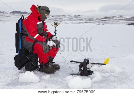 Man ice fishing on a cold winter day.