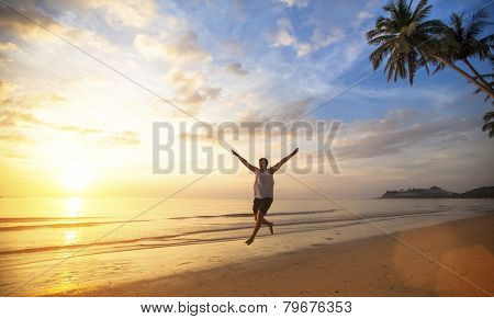 Young man jumping on ocean coast during amazing sunset. Long-awaited vacation concept.