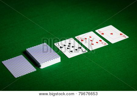 casino, gambling, poker, and entertainment concept - playing cards on green table surface