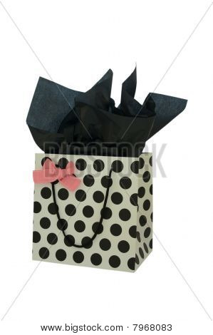 Black and white polka dot gift bag with pink bow and black tissue paper isolated on white background