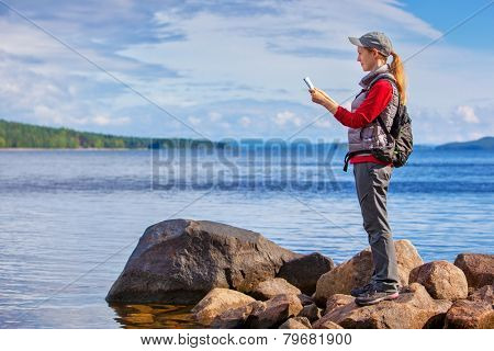 Young woman tourist with map and backpack standing on lake shore. Big rocks and wide lake on background.