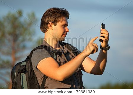 Young man tourist working with smartphone at travel outdoors. Searching route in navigator or making photos of location.