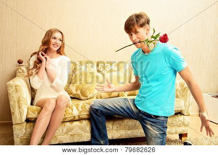Young man giving flowers to his sweetheart. They are in the cozy living room. Family, love concept.