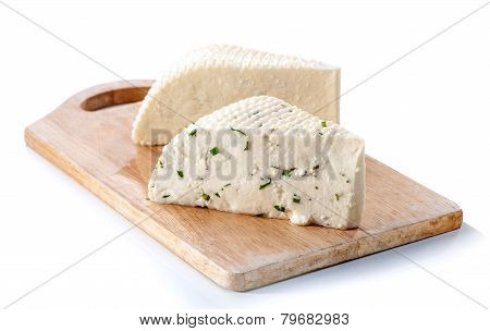 two varieties of soft cheese slabs on wooden board isolated