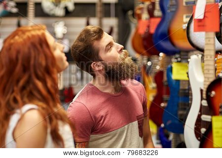 music, sale, people, musical instruments and entertainment concept - happy couple of musicians choosing guitar at music store