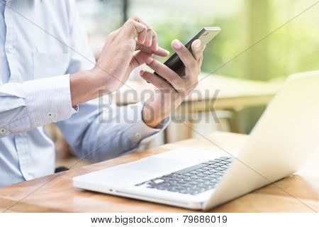 Asian Indian businessman using smartphone and laptop computer at outdoor cafeteria.