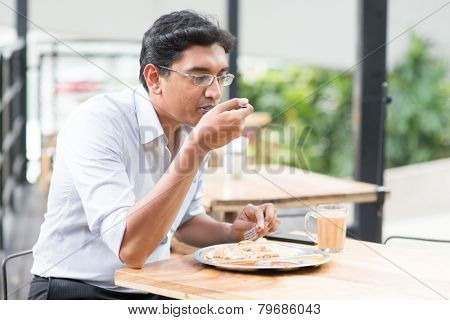 Asian Indian business man eating food at cafeteria.