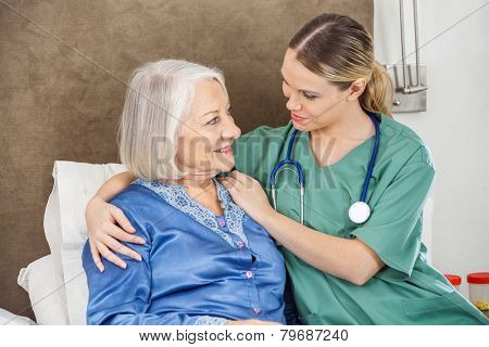 Female caretaker comforting senior woman in bedroom at nursing home