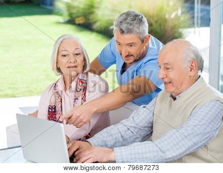 Male caretaker assisting senior couple in using laptop at nursing home porch