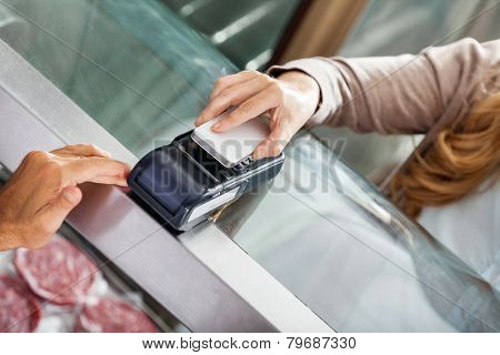 High angle view of female customer making payment through smartphone in butchery