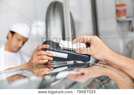 Cropped image of male customer paying through smartphone in butchery