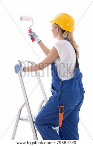 Young Woman Painter In Blue Builder Uniform Standing On Ladder With Paint Brush Isolated On White