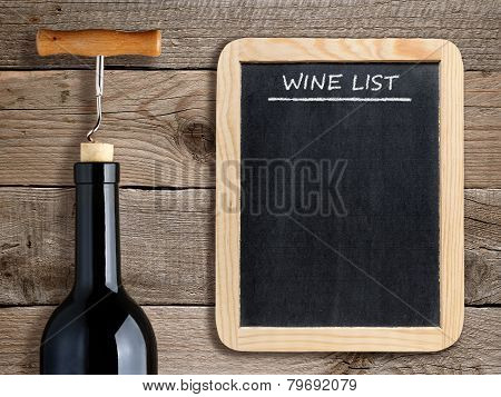 Wine List On Blackboard And Wine Bottle On Wooden Background