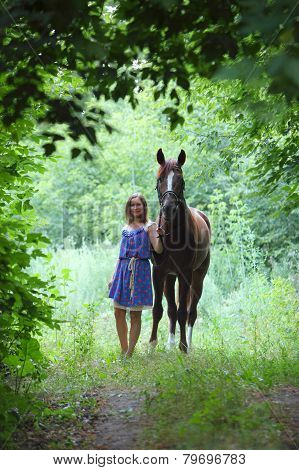 Happy woman posing with horse in forest