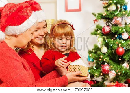 Mother and grandmother giving present to daughter