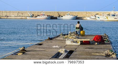 Fisherman sitting on the dock of harbor